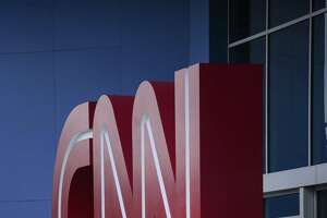 A pedestrian sits at CNN headquarters in Atlanta. Flip between CNN and Fox News and you'll see broadcasts that have become more partisan.
