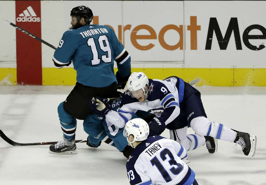 The Sharks' Mikkel Boedker and Jets' Andrew Copp (9) fall into Joe Thornton, who suffered a knee injury in the collision. Photo: Marcio Jose Sanchez, Associated Press