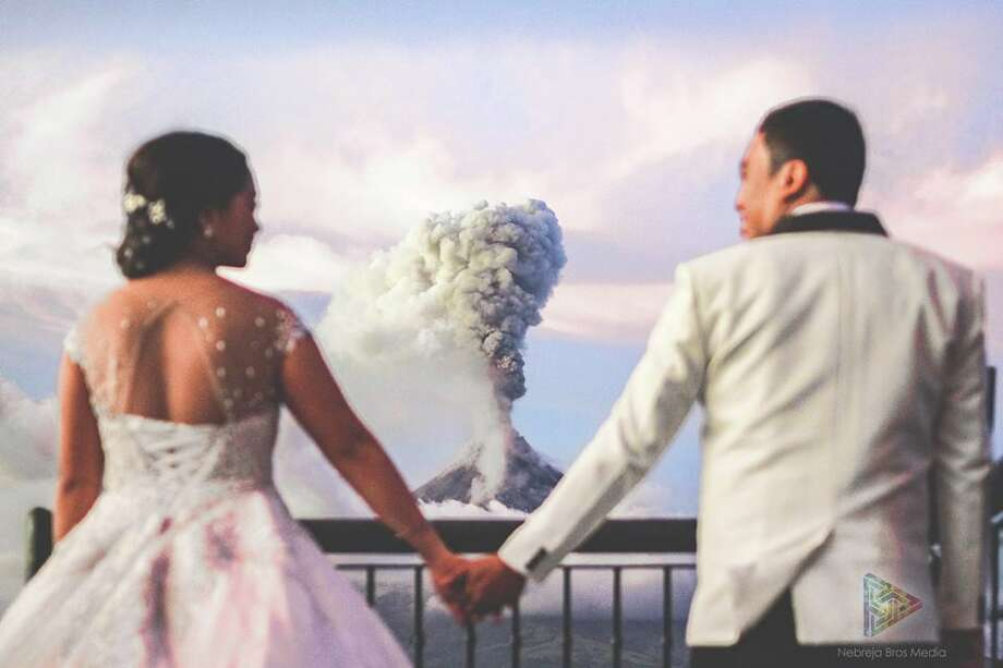 Arlo Gerald de la Cruz and Maria Hussa Maica Nicerio pose for wedding photos in front of a volcano. Click through the gallery to see the other photos. Photo: Nebreja Brothers Media Of Camalig Albay
