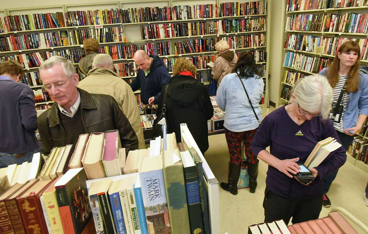 People browse for books at the winter used book sale at the Clifton Park-Halfmoon Library in 2018. Voters have overwhelmingly approved the library's 2022 budget. (Times Union file)