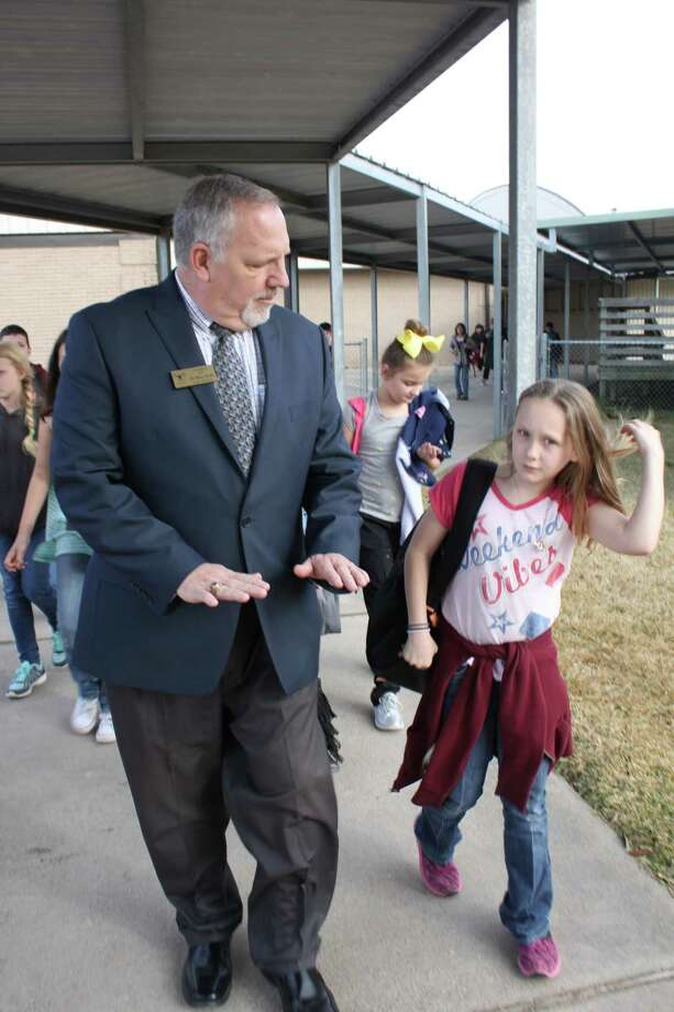 Tarkington ISD Superintendent Dr. Marc Keith answers a curious girl's question about a 'squishy' hole in the concrete that is used to access plumbing. No question is too big or small for Keith as he walks through the Tarkington Intermediate campus on Thursday. Photo: Vanesa Brashier