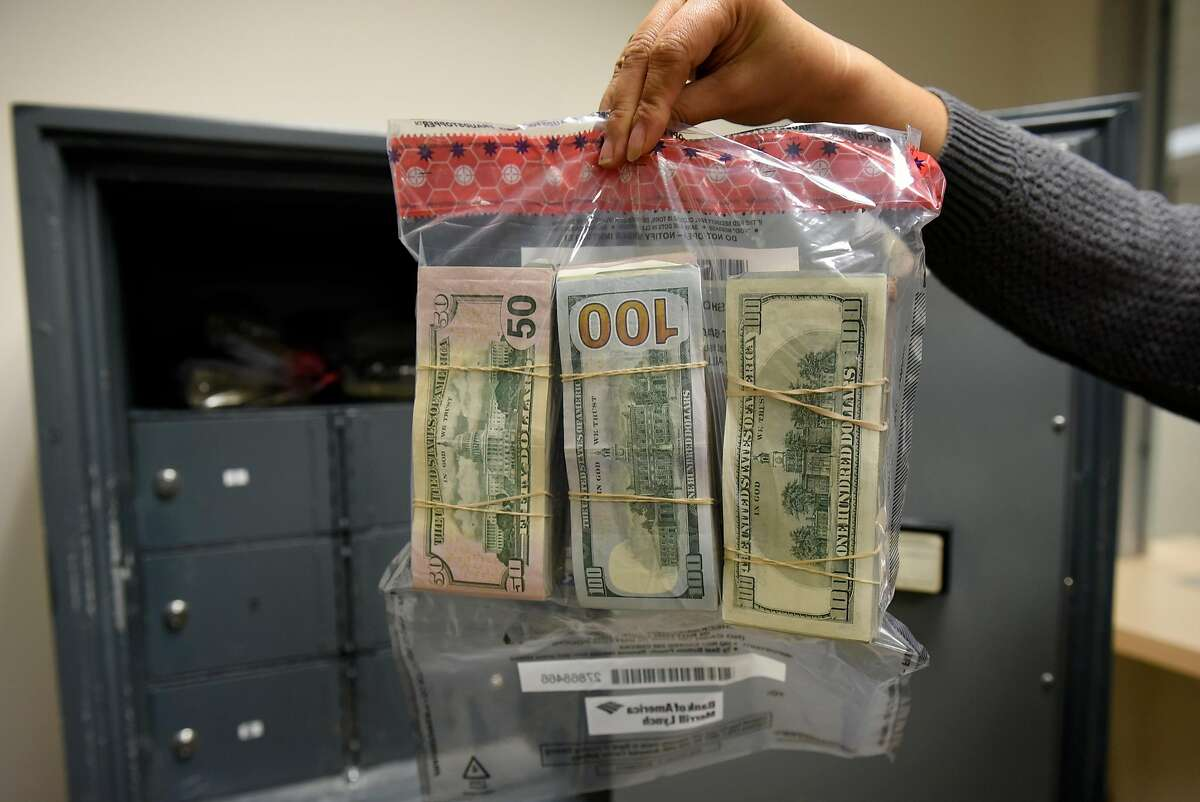 A cashier holds up a cash tax payment deposit made by a marijuana business, at the California Department of Tax and Fee Administration in Oakland, CA, on Monday November 27, 2017.