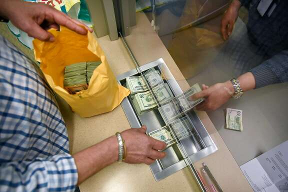 A marijuana business owner pays his taxes in cash at the California Department of Tax and Fee Administration in Oakland, CA, on Monday November 27, 2017.