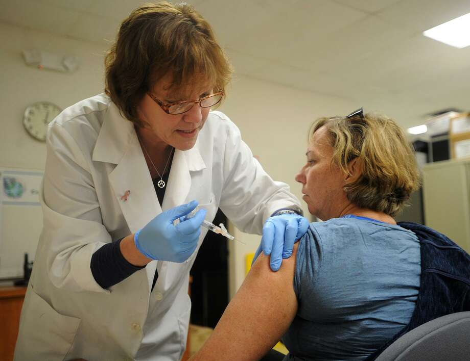 Public Health Nurse Linda Bespuda, RN, gives a flu shot to Linda Krol, of Milford, during a free flu shot clinic at Milford Health Department offices in Milford, Conn. on Wednesday, January 24, 2018. Photo: Brian A. Pounds / Hearst Connecticut Media / Connecticut Post