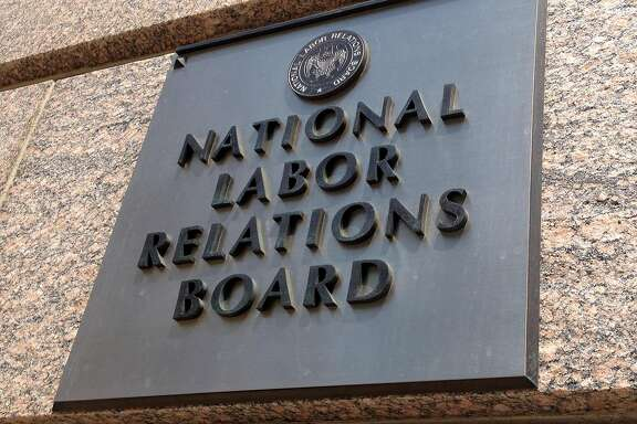 FILE - In this July 17, 2013 file photo, the sign for the National Labor Relations Board is seen on the building that houses their headquarters in Washington. The National Labor Relations Board issued a final rule on Friday aimed at modernizing and streamlining the union election process. The new rule will shorten the time between when an election is ordered and the election itself, eliminating a previous 25-day waiting period. And it seeks to reduce litigation that can be used to stall elections. It will also require employers to furnish union organizers with email addresses and phone numbers of workers. (AP Photo/Jon Elswick, File)