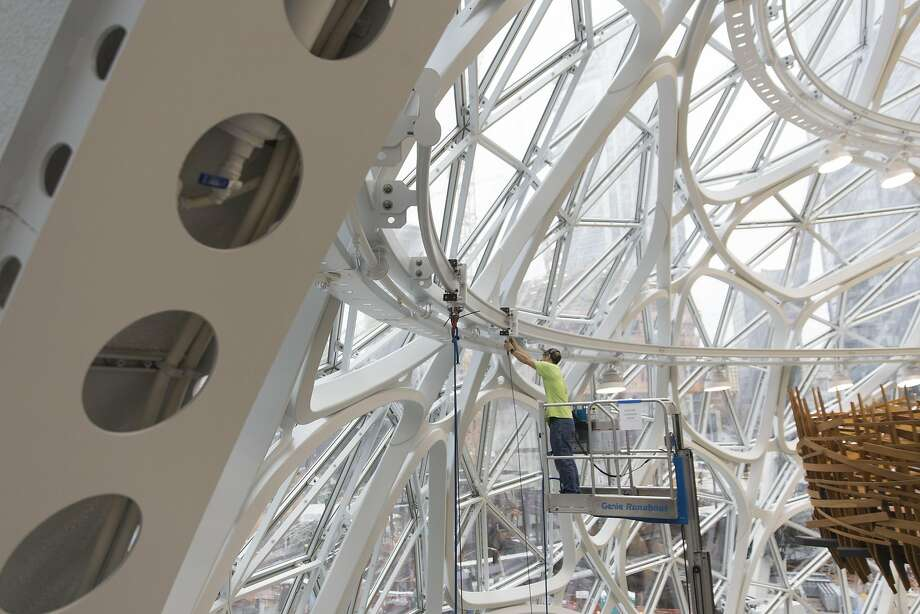 A worker stands on a cherry picker while making adjustments inside the Amazon.com Inc. Spheres before the opening in Seattle, Washington, U.S., on Tuesday, Jan. 23, 2018. The online retailer is scheduled to unveil the spheres Monday morning following seven years of planning and construction. The glass orbs have 40,000 plants from around the world. Photographer: Mike Kane/Bloomberg Photo: Mike Kane, Bloomberg