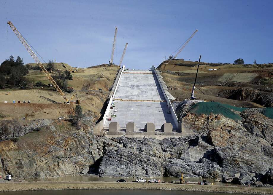 Part of the jump in costs to fix the Oroville Dam, shown in November, comes from the price of debris removal and building access roads for repair crews. Photo: Rich Pedroncelli, Associated Press