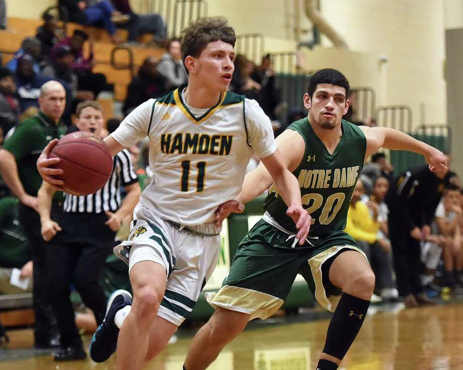 Hamden junior guard Victor Rosario drives past Notre Dame-West Haven senior forward Evan Blue, Friday, Jan. 26, 2018, at Hamden High School gymnasium. Hamden won, 67-62. Photo: Catherine Avalone, Hearst Connecticut Media / New Haven Register