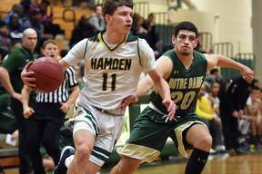 Hamden junior guard Victor Rosario drives past Notre Dame-West Haven senior forward Evan Blue, Friday, Jan. 26, 2018, at Hamden High School gymnasium. Hamden won, 67-62.