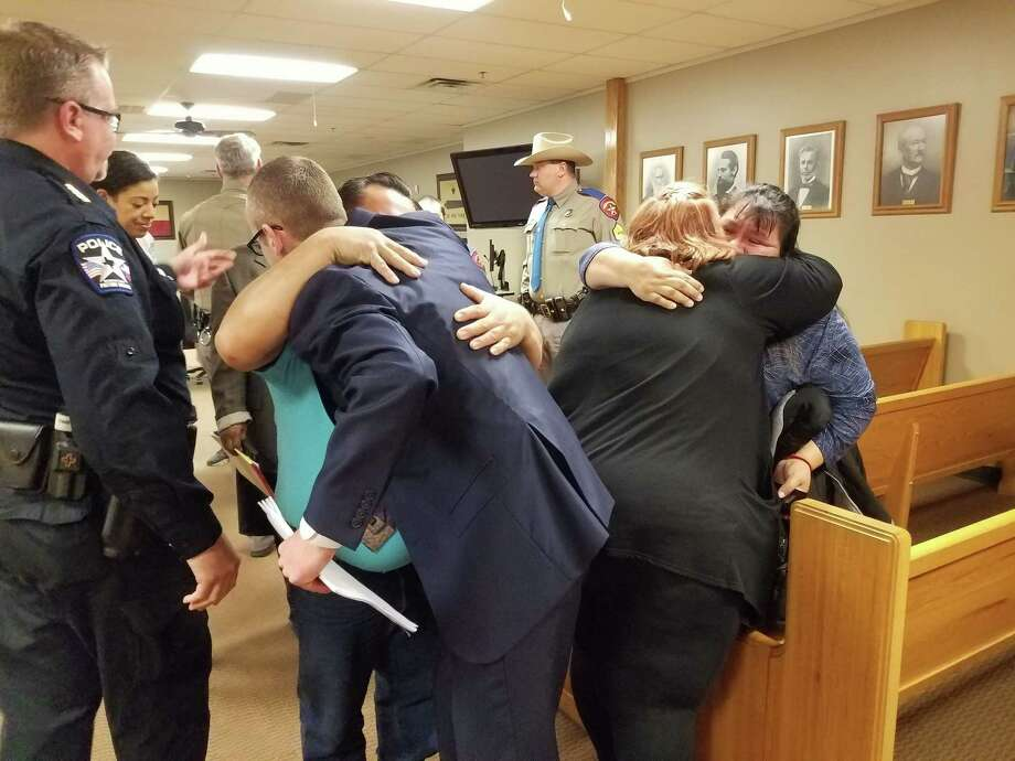 Members of the Baumgartner Family and the Hilario family hug after the guilty verdict was read for Garrett Nee of Kingwood Friday. Photo: Jennifer Summer