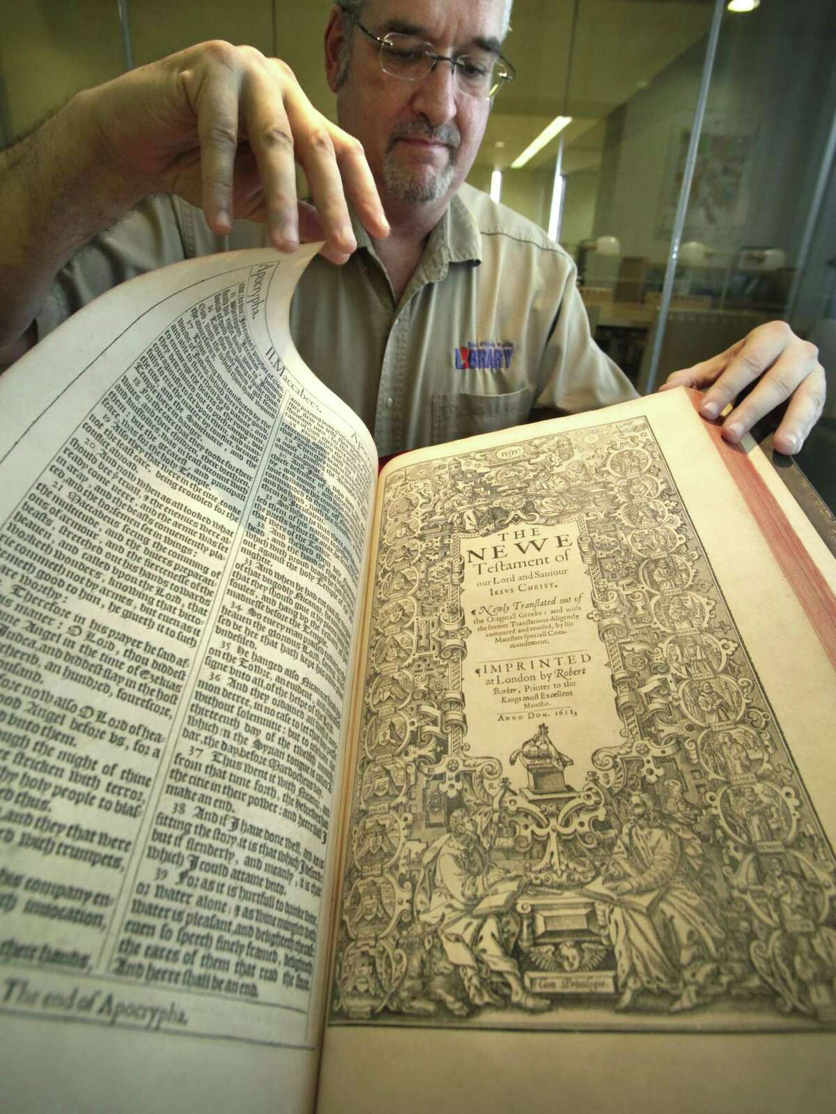 Matt DeWaelsche, assistant manager and archivist at San Antonio's Central Library, turns the page on the first-edition 1611 King James Bible, which was part of the library's collection in 2011, when it turned 400 years old.