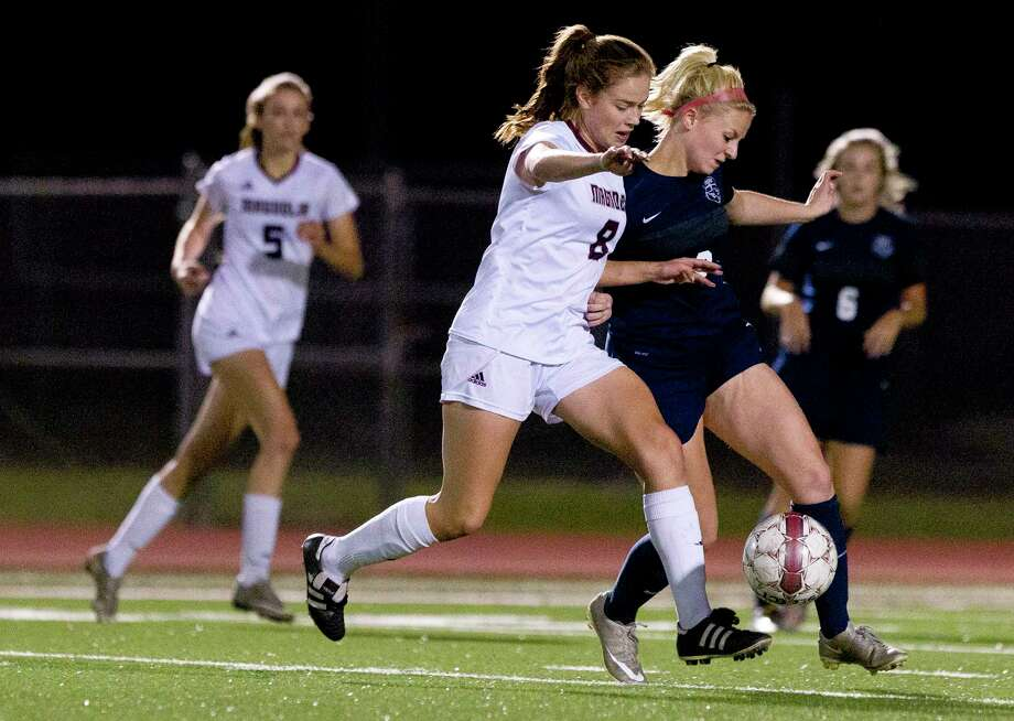 Magnolia midfielder Brooke Mallory (8) dribbles the ball against Tomball Memorial forward Gabbie Crenshaw (18) during the first period of a District 20-5A high school girls soccer match at Magnolia High School Friday, Feb. 3, 2017, in Magnolia. Magnolia defeated Tomball Memorial 3-0. Photo: Jason Fochtman, Staff Photographer / © 2017 Houston Chronicle