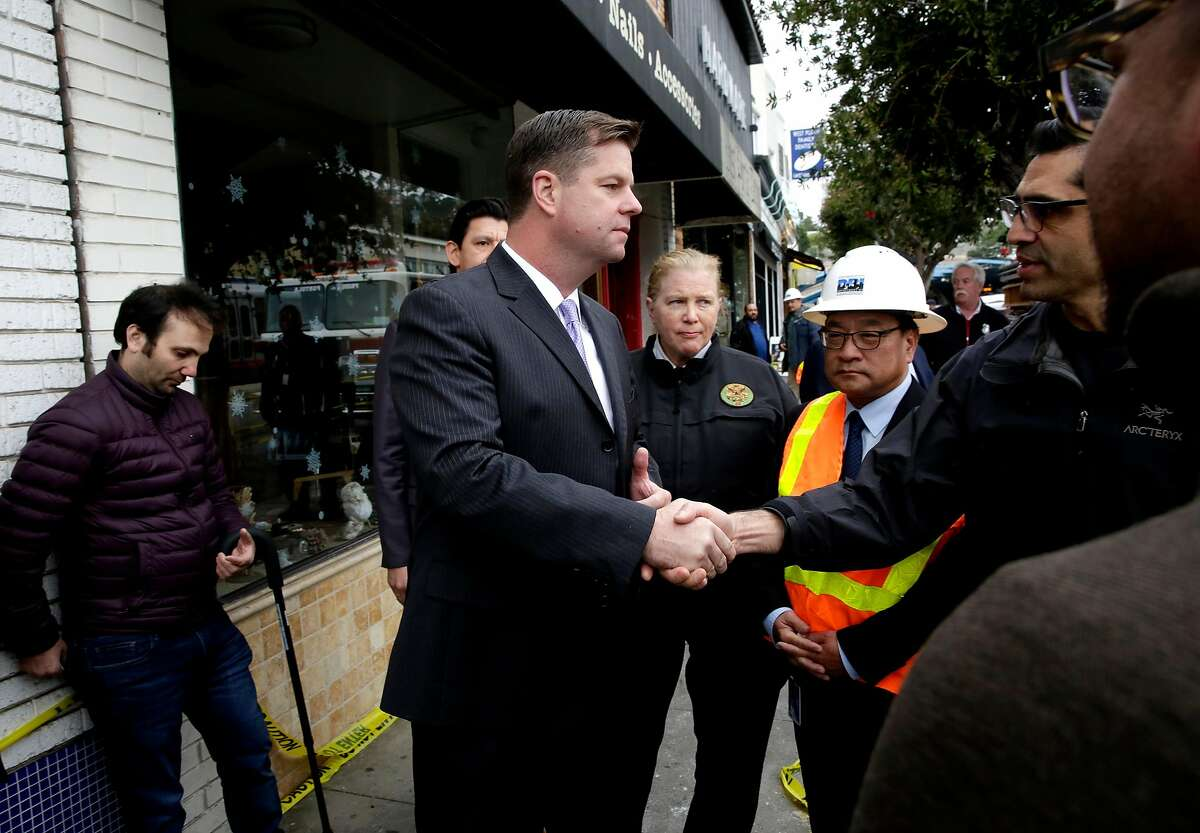 San Francisco Interim Mayor Mark Farrell visits the fire scene of an overnight blaze that destroyed a hardware store and several others were damaged, in San Francisco, Calif., as seen on Wednesday Jan. 24, 2018. Farrell talks meets Papenhausen hardware store manager Karl Aguilar, (right) and meet with other store owners as well. West Portal Daily market which was destroyed, the owner Issa Haddad is at left.