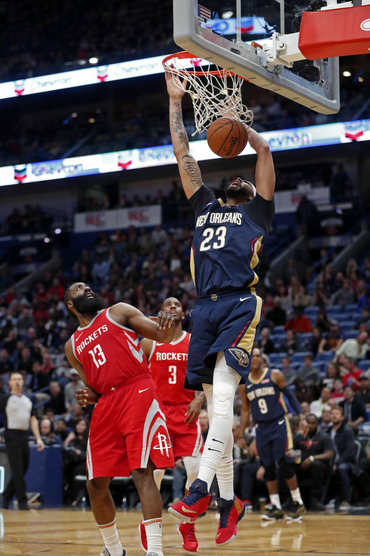 New Orleans Pelicans forward Anthony Davis (23) slam dunks over Houston Rockets guard James Harden (13) and guard Chris Paul (3) in the second half of an NBA basketball game in New Orleans, Friday, Jan. 26, 2018. The Pelicans won 115-113. (AP Photo/Gerald Herbert)
