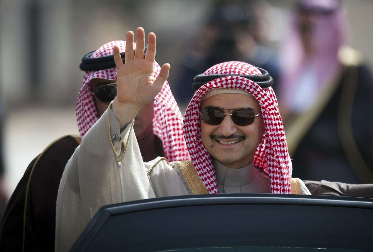 FILE - In this Feb. 4, 2014 file photo, Saudi billionaire Prince Alwaleed bin Talal waves as he arrives at the headquarters of Palestinian President Mahmoud Abbas in the West Bank city of Ramallah. Three associates of Saudi Prince Alwaleed bin Talal say the billionaire investor has been released after nearly three months in detention at a luxury hotel as part of an anti-corruption sweep. The associates told The Associated Press that the prince was released on Saturday Jan. 27, 2018. (AP Photo/Majdi Mohammed, File)