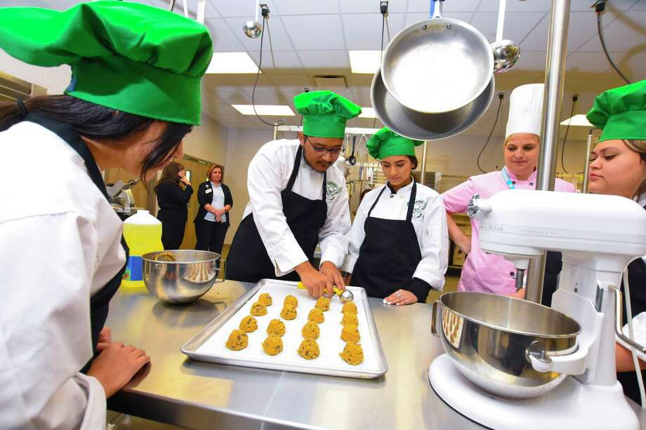 Klein Forest students Emily Martinez, Alan De La Rosa and Dayanara  Moreno put down the cookie dough on the cookie sheet for baking AS Instructed by chef Jennifer Rodgers And viewed by student Lourdes Menjivar. Photo: Tony Gaines, Photographer