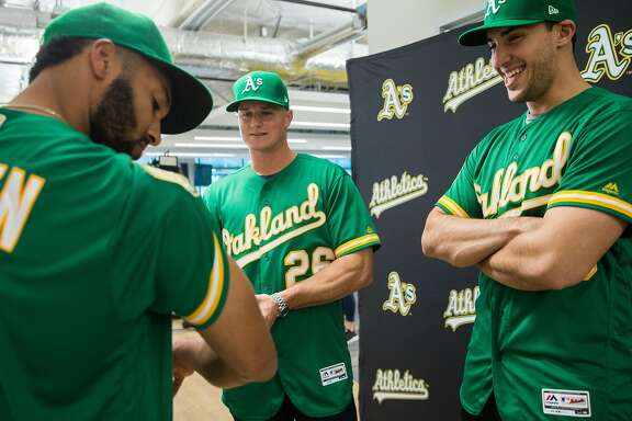 (From left) Oakland A's infielders Marcus Semien, Matt Chapman, and Matt Olson sport the 50th Anniversary edition jersey during a fashion show at the Oakland A's Headquarters Friday, Jan. 26, 2018 in Oakland, Calif.