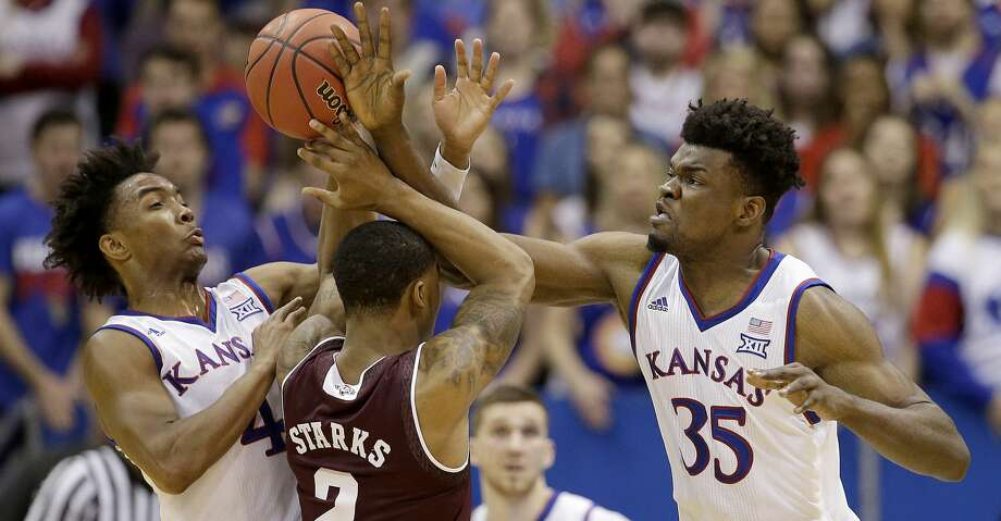 Kansas' Devonte' Graham (4) and Udoka Azubuike (35) knock the ball away from Texas A&M's TJ Starks (2) during the first half of an NCAA college basketball game Saturday, Jan. 27, 2018, in Lawrence, Kan. (AP Photo/Charlie Riedel) Photo: Charlie Riedel/Associated Press
