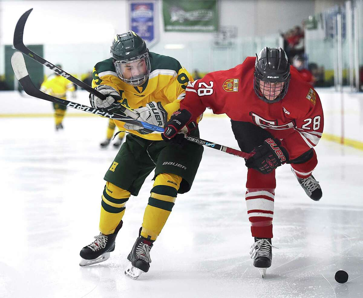 Hamden junior forward Eddy Fracasso and Fairfield Prep junior defenseman Connor Boyle battle for a loose puck, Saturday, Jan. 27, 2018, at Astorino Rink in Hamden. The Jesuits shout out the Green Dragons, 4-0.