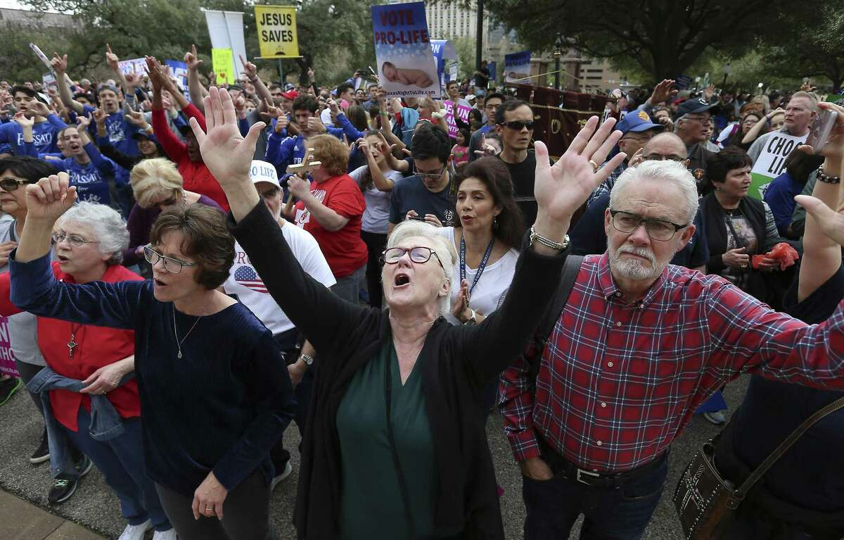 Jan Madden (center) of Austin raises her hands in praise as The Texas Rally for Life brought a large crowd to march and gather at the Texas Capitol where they heard Texas Gov. Greg Abbott support pro-life and laws that benefit pro-life in Austin on Saturday, Jan. 27, 2018. (Kin Man Hui/San Antonio Express-News)
