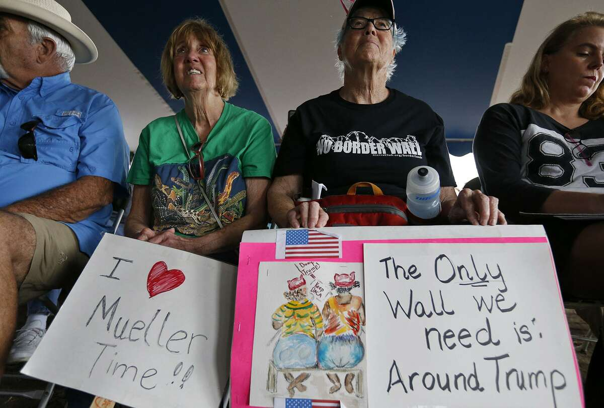 Sharon Spencer, 71, of Marble Falls (left) and Kay Smith, 69, of Austin, have signs stating their views.