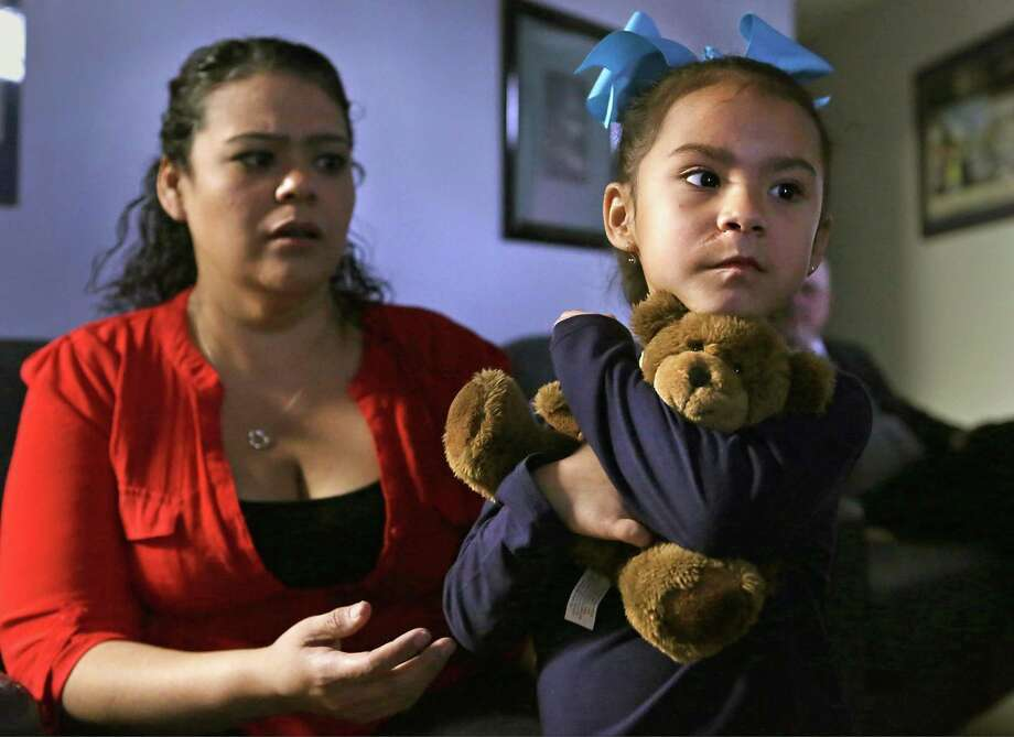 Clutching her security teddy bear and sitting in her mother's, Tanisha Garcia, lap, Abbey Garcia, 5, right, recalls the attacked by a dog. Photo: Bob Owen, Staff / San Antonio Express-News / ©2018 San Antonio Express-News