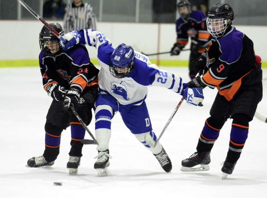 Westhill-Stamford Co-op Jason Marchese (24) and Tyler Tuccinadri (9) battle for the puck with Darien Bennett McDermott (22) during a FCIAC boys hockey game at the Darien Ice House in Darien, Conn. on Saturday, Jan. 27, 2018. Photo: Matthew Brown / Hearst Connecticut Media / Stamford Advocate