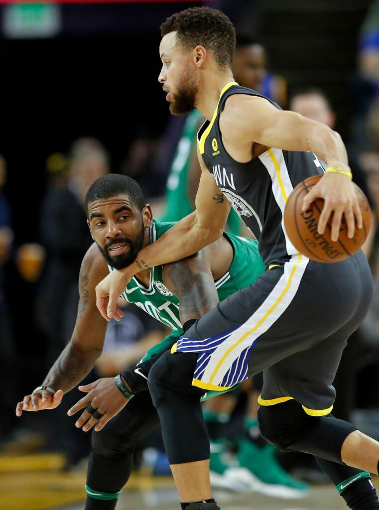 23dfc686bfd6 Golden State Warriors  Stephen Curry wards off a defensive challenge from Boston  Celtics  Kyrie