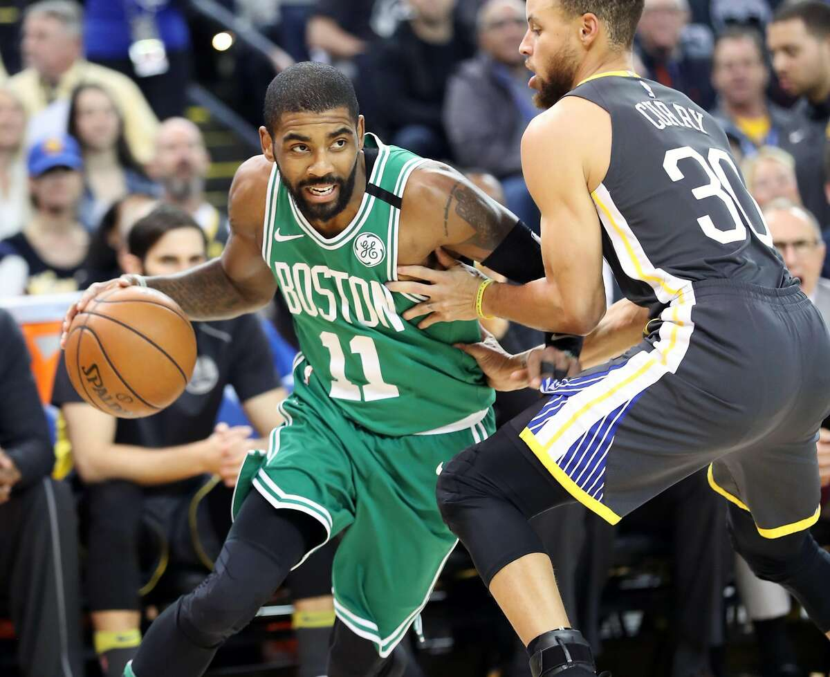 Boston Celtics' Kyrie Irving drives against Golden State Warriors' Stephen Curry in 1st quarter during NBA game at Oracle Arena in Oakland, Calif., on Saturday, January 27, 2018.