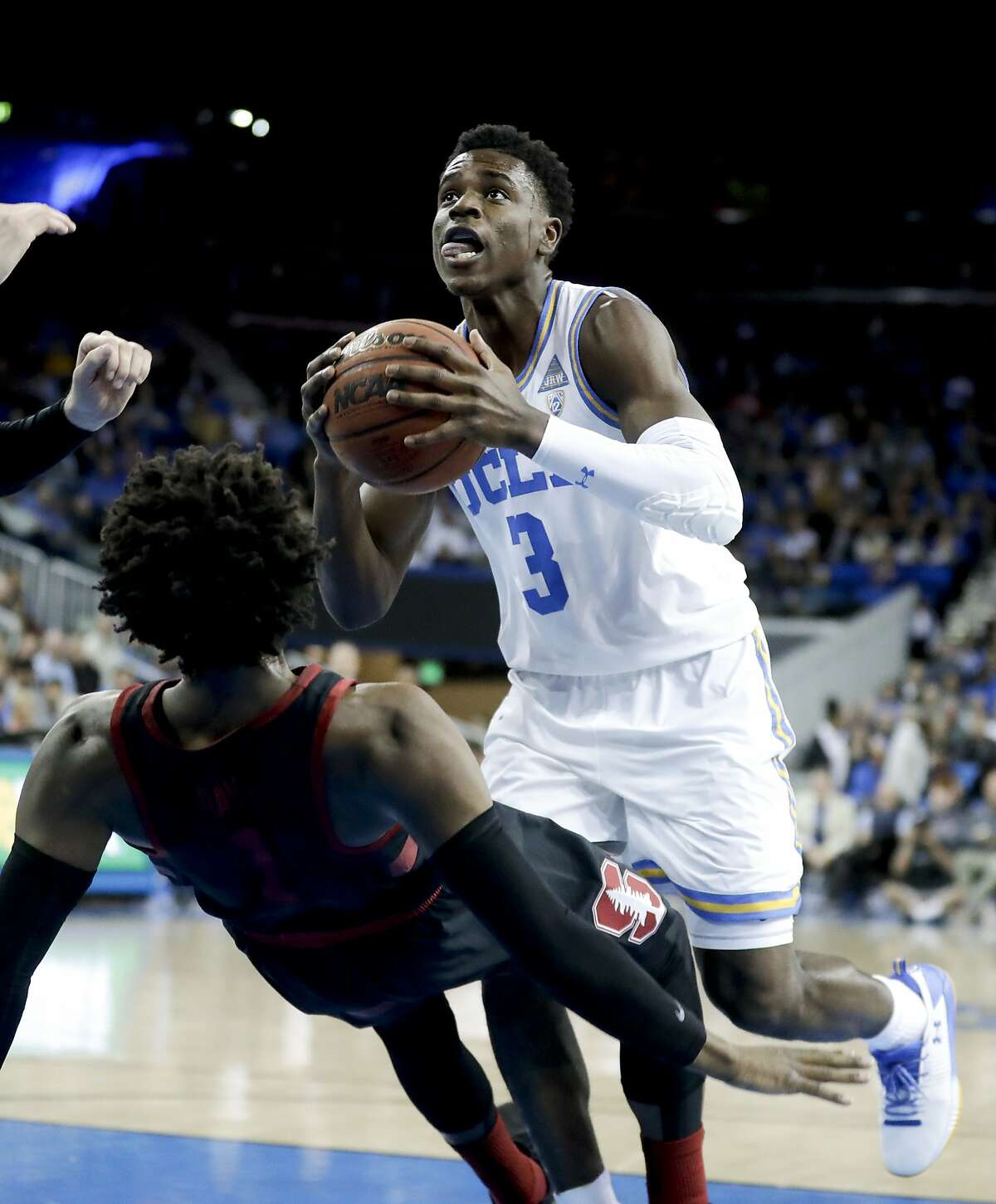 UCLA guard Aaron Holiday looks to shoot as Stanford guard Daejon Davis falls during the first half of an NCAA college basketball game in Los Angeles, Saturday, Jan. 27, 2018. (AP Photo/Chris Carlson)