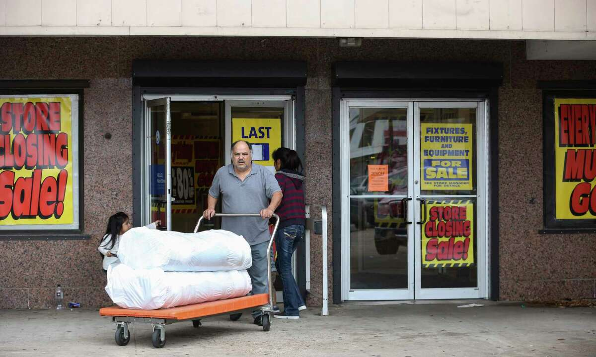 A Sears staff at the Main Street location helps customers to wheel purchased rugs to the parking lot on Sunday, Jan. 28, 2018, in Houston. Sunday was the department store's last open day.