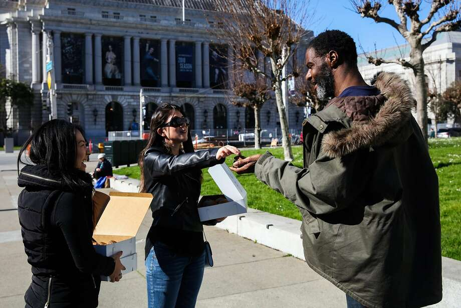 Rebecca Han (left) and Elissa Jennings hand Broderick Robinson a freshly baked muffin on Grove Street in San Francisco. Photo: Gabrielle Lurie, The Chronicle