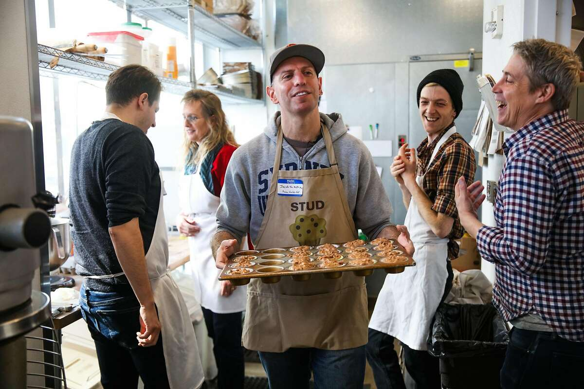 Jacob Kaufman (center) carries a pan of uncooked muffins to the oven while baking muffins for the homeless at Hayes Valley Bakeworks in San Francisco, California, on Sunday, Jan. 28, 2018.