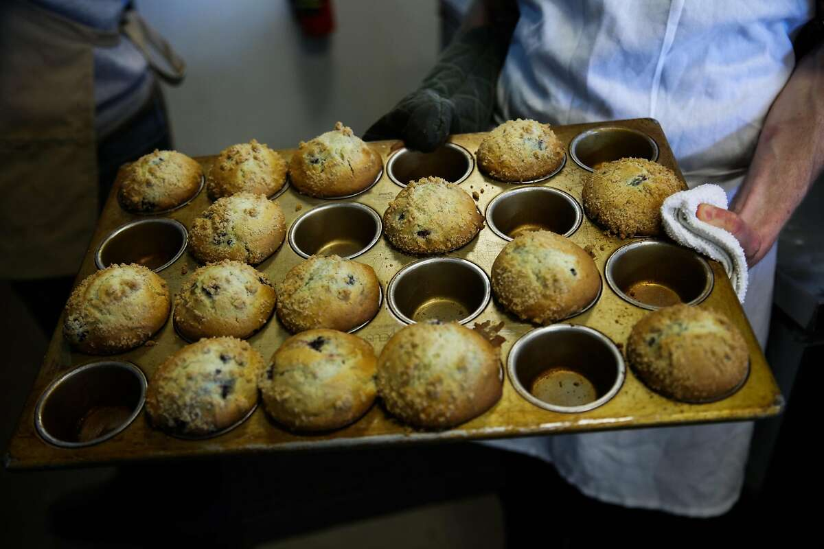 Zak McLongstreet holds a pan of freshly baked muffins at Hayes Valley Bakeworks.