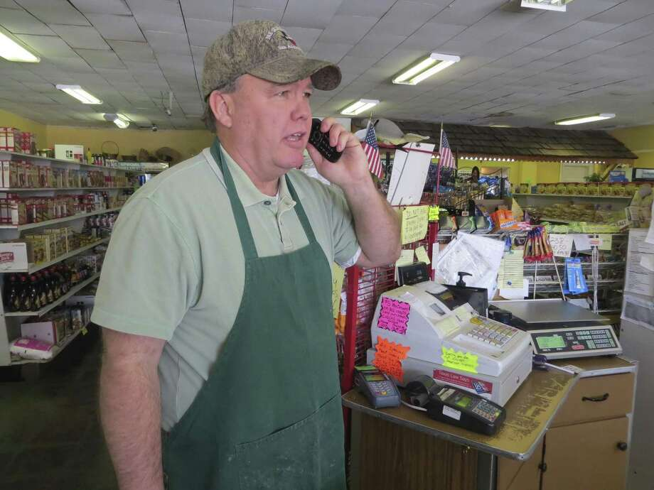 John Sheffield, a grocer in Ingram, talks on the phone in his store. Sheffield contends city officials there have overstepped their authority by trying to force him to tie his business into a new sewer main, as required by city ordinance. Photo: Zeke MacCormack /San Antonio Express-News / San Antonio Express-News