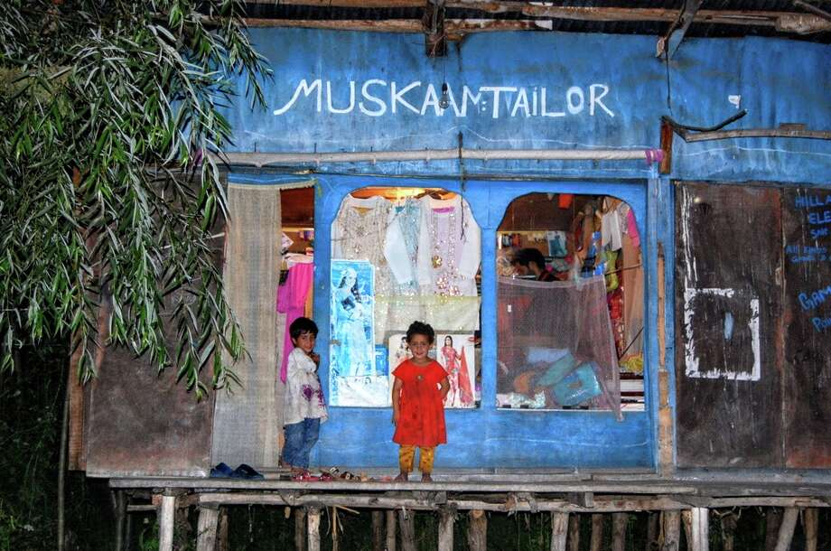 Children stand outside their home and family's tailor shop on the Dal lake in Kashmir, India. Photo: Olivia P. Tallet