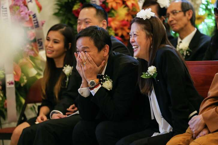 Richard Lam, Soonkack Kook and Michelle Lam react as attendees share loving anecdotes during the memorial service for their parents Bao and Jenny Lam on Sunday, Jan. 28, 2018, at Winford Funeral Home in Houston.