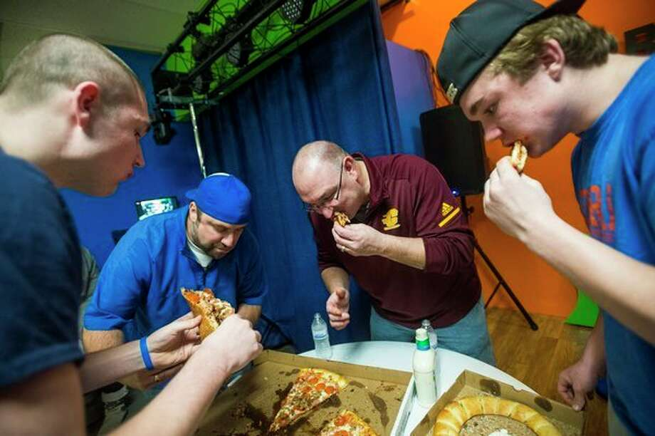 All you can eat From left, Jerry Bringard, 18, Seth Freed, 41, John Bringard, 50, and Jack Bringard, 17, compete in a pizza eating contest on Saturday at Code Breakers Escape and Puzzle Rooms. (Katy Kildee/kkildee@mdn.net)