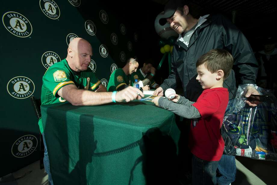 New Oakland Athletics third base coach Matt Williams, left, signs a ball for five-year-old Kyle Sanchez of Martinez, Calif. while dad Daniel watches, during Oakland Athletics Fan Fest at Jack London Square on Saturday, Jan. 27, 2018 in Oakland, Calif. Photo: D. Ross Cameron, Special To The Chronicle