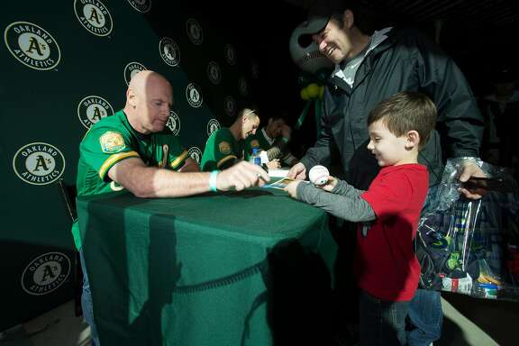 New Oakland Athletics third base coach Matt Williams, left, signs a ball for five-year-old Kyle Sanchez of Martinez, Calif. while dad Daniel watches, during Oakland Athletics Fan Fest at Jack London Square on Saturday, Jan. 27, 2018 in Oakland, Calif.