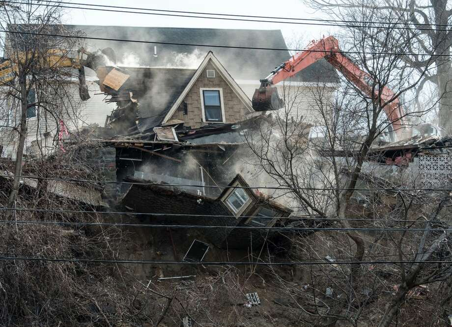 Part of 15 Barney St., Schenectady fell down the hill above Nott Terrace as crews on Monday razed the two-story home that was undermined by Sunday's collapse of the hillside beneath it. Photo: Skip Dickstein / Times Union