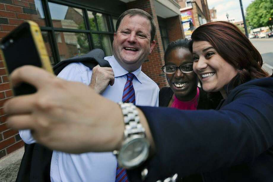 Erin Stewart, right, takes a selfie with former state Senate GOP Leader John McKinney during the 2014 governor's race. Photo: AP Photo