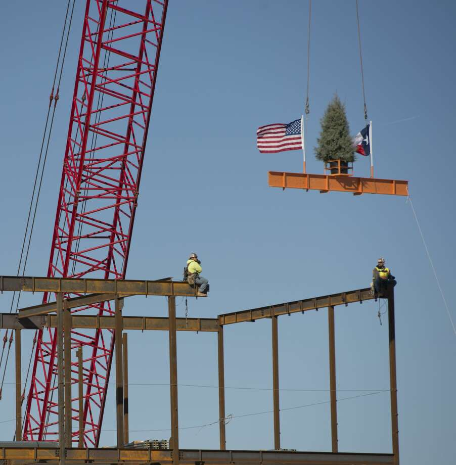 "Workers position the final beam into place 01/29/18 during the ""topping out"" ceremony for the new engineering building at UTPB. Tim Fischer/Reporter-Telegram Photo: Tim Fischer/Midland Reporter-Telegram"