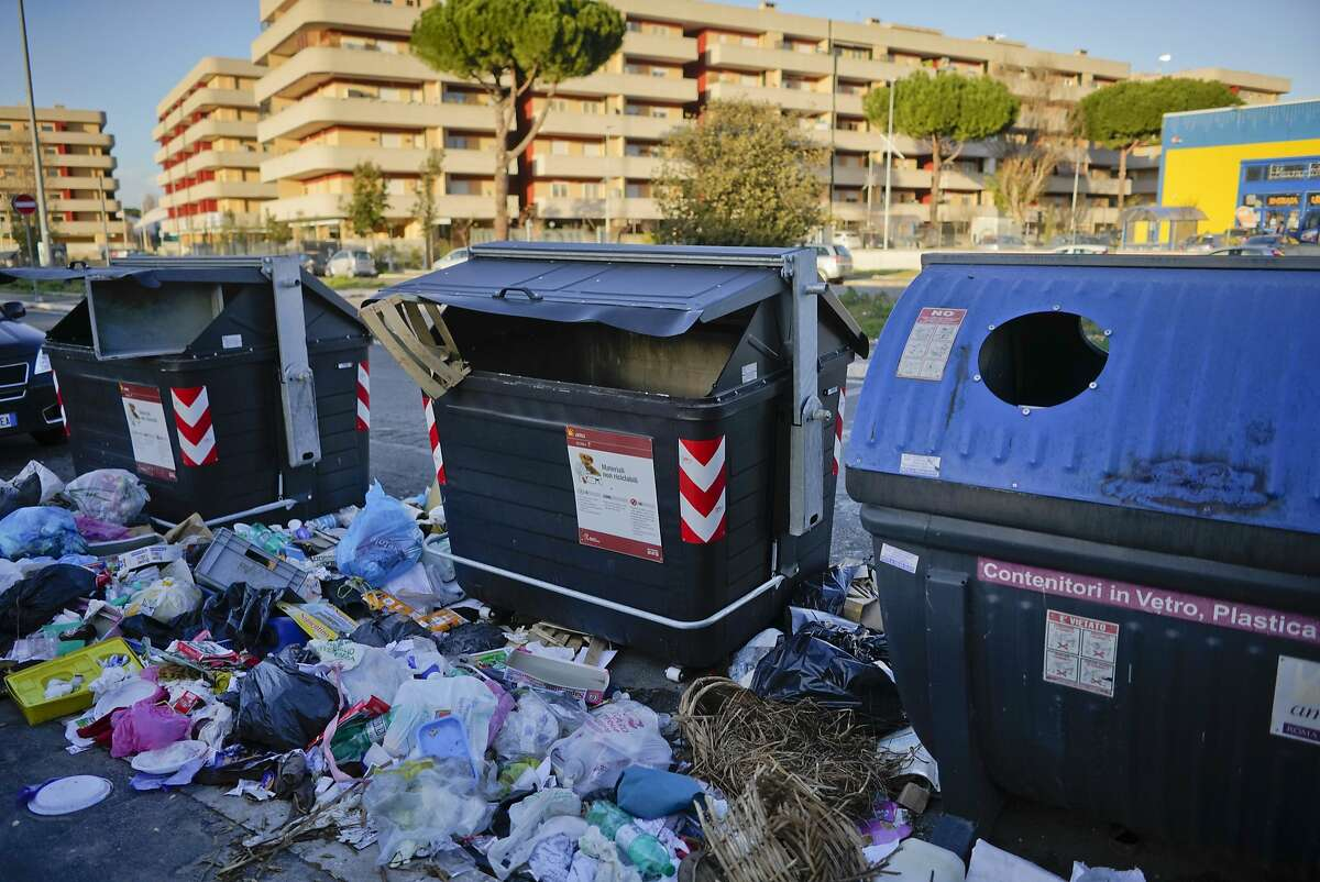 Trash surrounds garbage bins, in Rome, in this photo taken on Wednesday, Jan. 17, 2018. On March 4, Italians will cast ballots for Parliament, a national election that will also help determine their new government. Rome's mayor isn't running at all, but that detail hasn't stopped politicians from transforming the city's chronic trash problem into a big campaign trail issue. (AP Photo/Andrew Medichini)