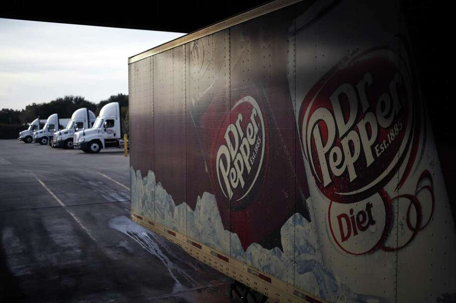 Signage for Dr Pepper soda is displayed on a delivery truck outside the Dr. Pepper Snapple Group Inc. bottling plant in Irving, Texas, U.S., on Tuesday, Oct. 25, 2016. Keurig Green Mountain Inc., known for its single-serve coffee brewers, will take control of Dr Pepper Snapple Group Inc. The deal will pay $18.7 billion in cash to shareholders and assemble a massive beverage distribution network in the U.S., giving JAB Holding Co businesses even greater control over how Americans eat and drink. Our editors select the best archive images on the Dr Pepper brands. Photo: Luke Sharrett /Bloomberg / © 2016 Bloomberg Finance LP