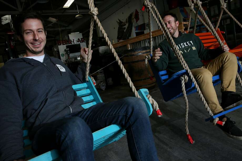Seven Stills owners Tim Obert (left) and Clint Potter ride the swings at the bar. Photo: Santiago Mejia, The Chronicle