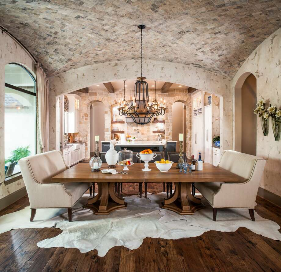 This dining area designed by Chairma Design Group has a double barrel vaulted ceiling covered in natural stone. Animal skin rugs cover the hardwood flooring and two settees provide seating at the dining table. Photo: Courtesy Photo