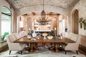 This dining area designed by Chairma Design Group has a double barrel vaulted ceiling covered in natural stone. Animal skin rugs cover the hardwood flooring and two settees provide seating at the dining table.