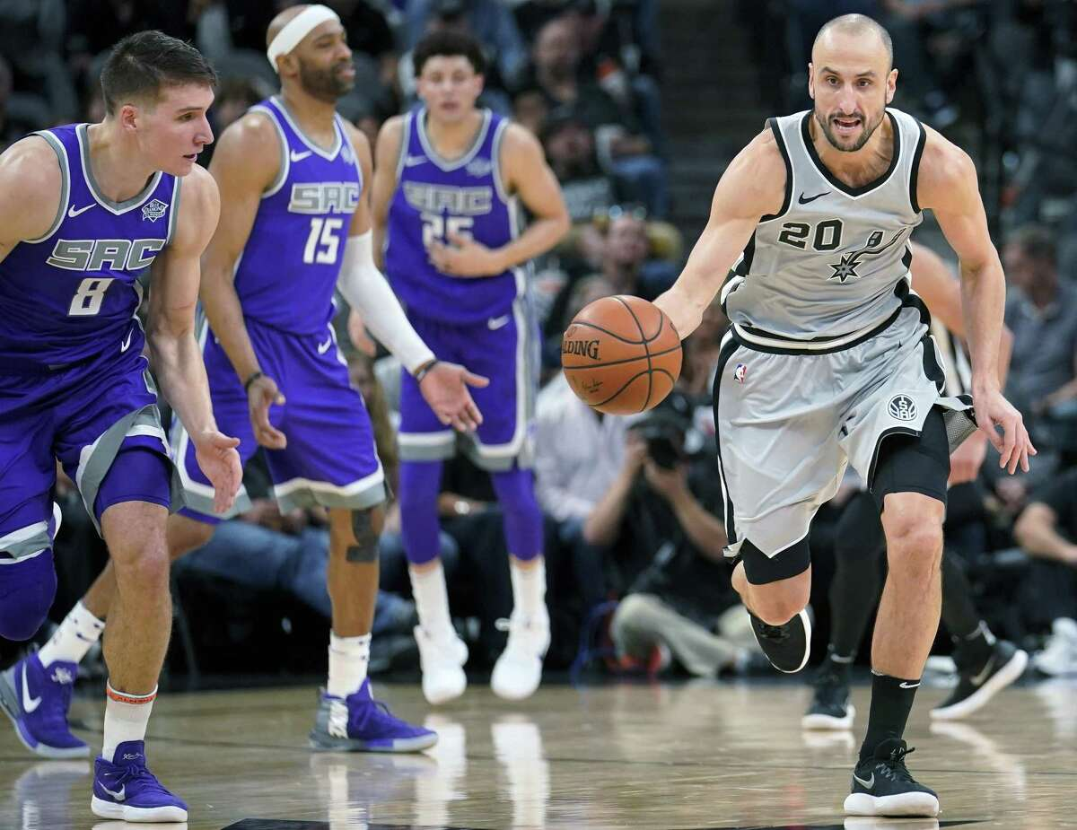San Antonio Spurs' Manu Ginobili (20) steals the ball as Sacramento Kings' Bogdan Bogdanovic (8) looks on during the second half of an NBA basketball game, Sunday, Jan. 28, 2018, in San Antonio. San Antonio won 113-98. (AP Photo/Darren Abate)
