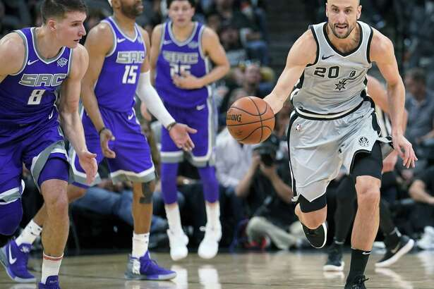 San Antonio Spurs' Manu Ginobili (20) steals the ball as Sacramento Kings' Bogdan Bogdanovic (8) looks on during the second half of an NBA basketball game, Sunday, Jan. 28, 2018, in San Antonio. San Antonio won 113-98. (AP Photo/Darren Abate)